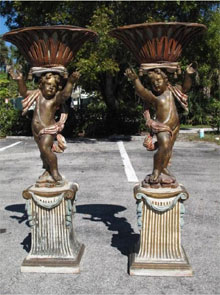Pair of rare, latter 19th-century Venetian parcel gilt and polychrome painted wood putti, each 57 inches tall and holding a reticulated carved wood cache pot with original tole liners. Estimate for pair $7,000-$9,000. Auctions Neapolitan image.