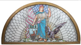 Half-round leaded-glass window featuring Liberty figure, from a Hartford Insurance Co. building, 82in. wide by 44in. tall, est. $7,000-$10,000. Noel Barrett Auctions image.
