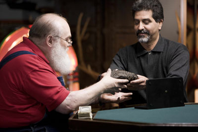 Las Vegas dealer Glen Parshall (left) considers making a cash offer on a fossilized woolly mammoth tooth brought in during the taping of 'Real Deal,' HISTORY Channel's new auction house reality show based at Don Presley Auctions in Orange, Calif. Image courtesy of HISTORY.
