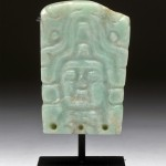 Apple-green jade adornment with carved visage of Mayan ruler or lord wearing headdress, 6th-9th century CE, estimate 4,000-$6,000.